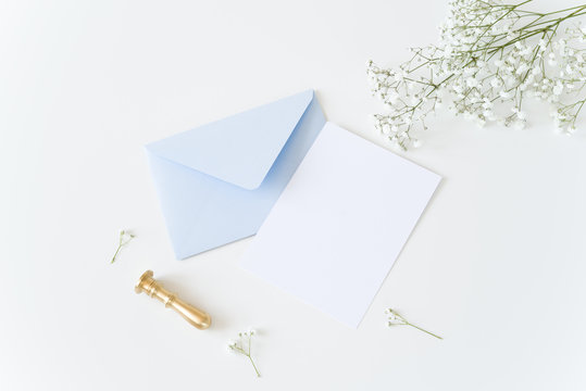 White and blue wedding stationery. Blank greeting card, craft envelope, washi tape and golden stamp, binder clips with olive branch.White table background. Flat lay, top view.