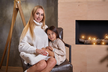 Beautiful mother woman in white sweater hugs her little daughter. Cheerful playful mood and love inside the family.