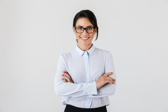 Photo of pretty businesslike woman wearing eyeglasses standing in the office, isolated over white background