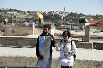 Tour guide Noor Awad, a Palestinian from Bethlehem, holds a map of Israel as he stands next to his colleague Lana Zilberman Soloway, a Jewish seminary student, during the Dual Narrative tour in Jerusalem's Old City