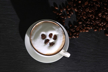 Milchschaum in einer Tasse garniert mit Kaffeebohnen