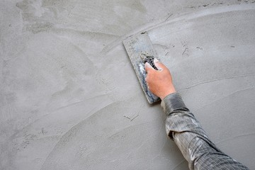 Plasterer man hand using trowel to plastering cement on concrete wall