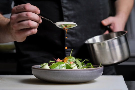 Close-up of the hands of a male chef on a black background. Pour sauce from the spoon on the salad dish.