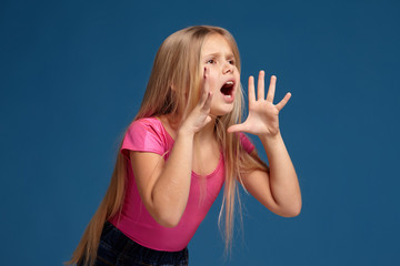 Portrait of emotional little girl on blue background