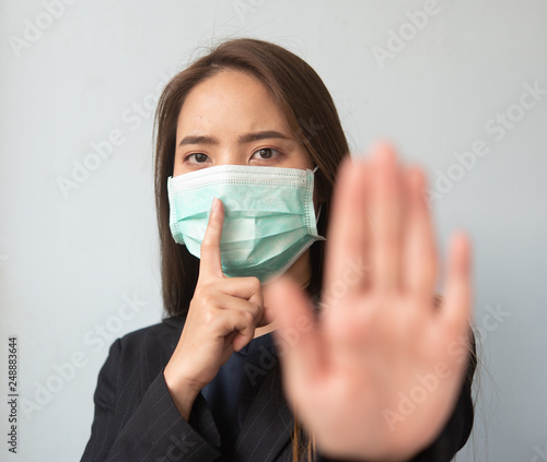 Women wearing dust masks Use the hand to display anti-symbols and