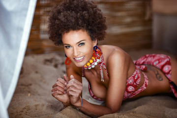 Beauty photo of natural girl with afro lying on sand