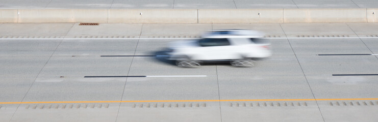 A blurred motion photo of a white SUV on a highway.