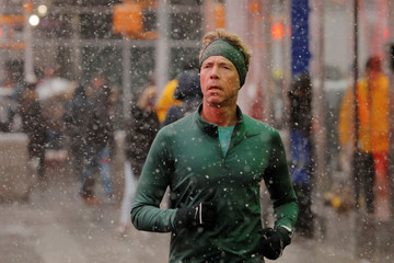 A runner jogs down the sidewalk as snow falls in the Times Square neighborhood of New York