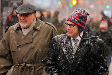 Pedestrians walk down the sidewalk as snow falls in the Times Square neighborhood of New York