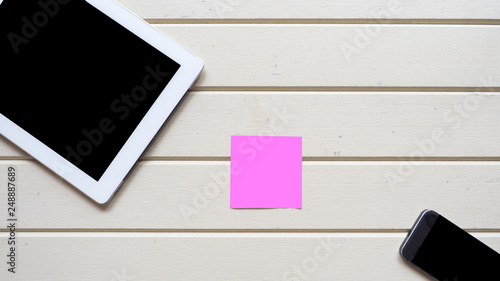 Wall mural taplet with smart phone and post it topview on wood background