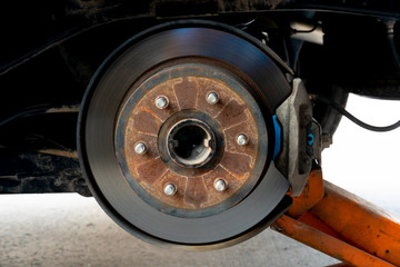 Remove the tire to repair something close up pitch circle diameter with disk break and caliper. Car maintenance for safety before departure. And jack up the car.