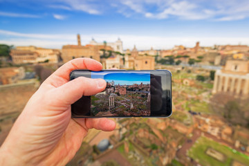 Hand with mobile camera making photo of the Roman Forum in Rome, Italy