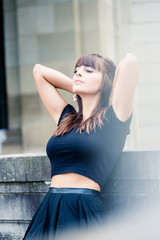 Beautiful young woman leaning on wall