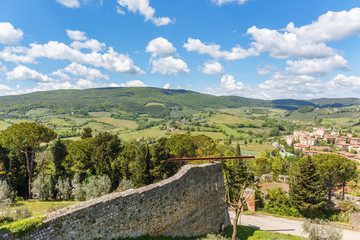 Landscape view of a rolling Tuscan landscape with a city wall