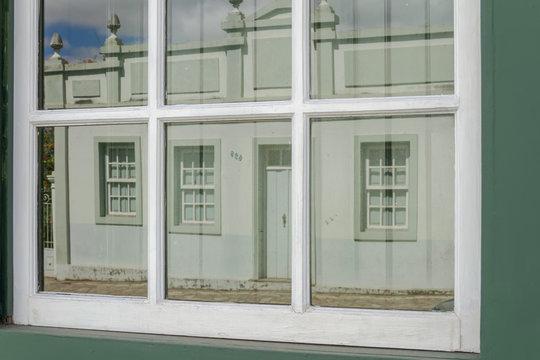 Detalhe de janela colonial com reflexo de casa colonial de Santa Luzia, estado de Minas Gerais., Brasil.