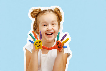 Cheerful little girl child shows hands painted with paint. Blue background, portrait