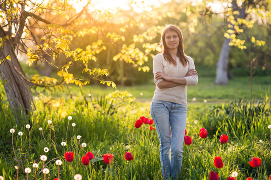 young woman  standing on a clearing of green grass with blooming tulips at sunset