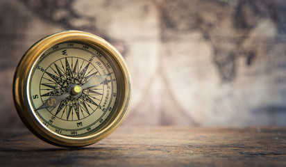 Old compass on vintage map background.