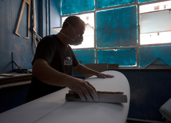A man uses hand tools and light from the window as he shapes a surfboard at Spider Performance Surfboards in Durban