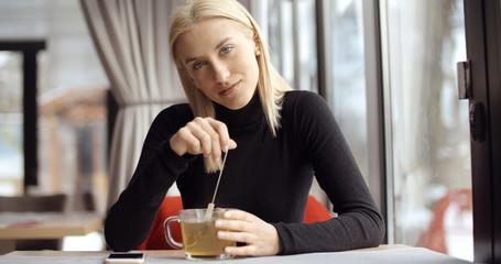 Young girl enjoying her tea in restaurant.