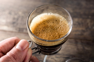 Man holding coffee glass and coffee grain on wooden table.