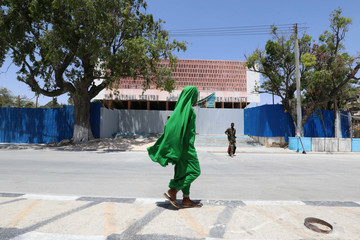 A woman walks past Somalia's National Theatre as it undergoes a renovation project in Mogadishu