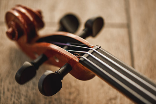 Construction of violin. Top view of the violin neck lying on wooden background