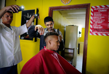 A barber cuts hair by torch lights from mobile phones during electricity load-shedding in Cape Town