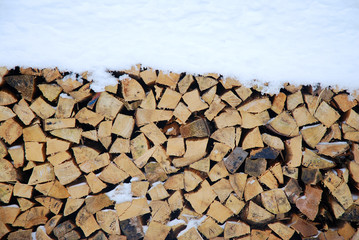 Stack of fire wood in covered with snow