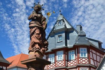 Brunnenstatue Maria Immaculata als Brunnensäule mit goldener Lilie und Strahlenkranz in der historischen Altstadt am Großen Markt von Heppenheim an der Bergstraße, Hessen, Deutschland