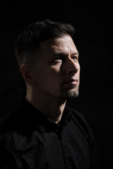 Portrait of a handsome man 40 years old on a dark artistic background close-up. Brunette, with gray hair, black beard and black shirt.