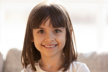 Cute little girl smiling looking at camera indoors, headshot portrait