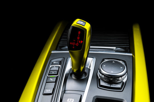 Yellow Automatic gear stick of a modern car. Modern car interior details. Close up view. Car detailing. Automatic transmission lever shift isolated on black background. Black leather interior