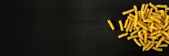 farfalle Raw Fusilli italian pasta on a wood black textured background. Close-up view from the top. Free space for text. banner