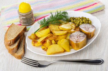 Bread, plate with slices of fried potatoes, smoked mackerel, green peas, dill, pepper shaker on napkin, fork on table