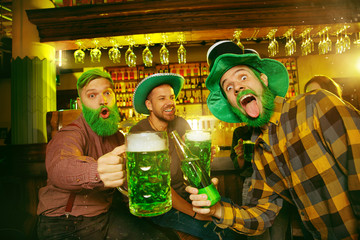 Saint Patrick's Day Party. Happy friends are celebrating and drinking green beer. Young men and women wearing green hats. Pub Interior.