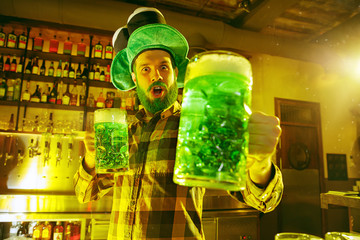 Happy man with glass of green beer looking aside in pub. Saint Patrick's Day Party