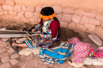 Peruvian women sitting on ground weaving