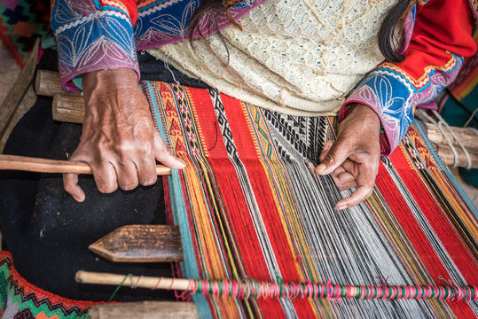 Hands of Peruvian weaver making a striped textile