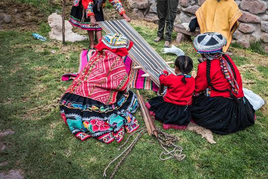 Several Peruvian women weaving a long striped textile