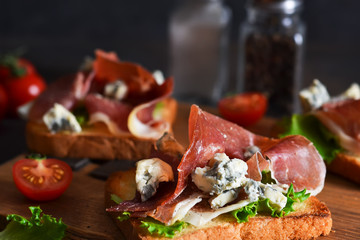 Bruschetta with prosciutto, salad frieze and cheese on the kitchen table. Snack.