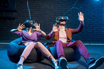Man and woman touching space while playing in virtual reality using VR headsets in the playing room