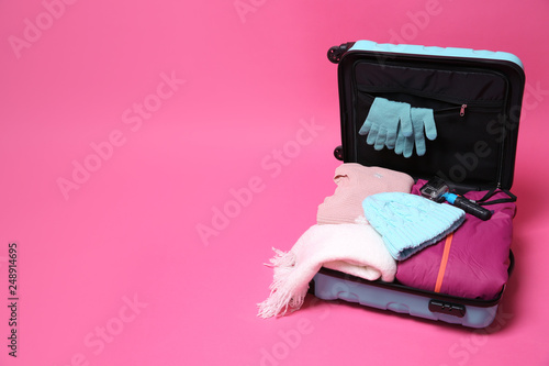 d4d809ee5a1 Open suitcase with warm clothes and action camera on color background