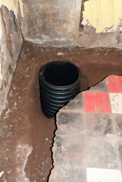 An open french drain pit and sump pump basin prior to being filled with stones and  covered with concrete.