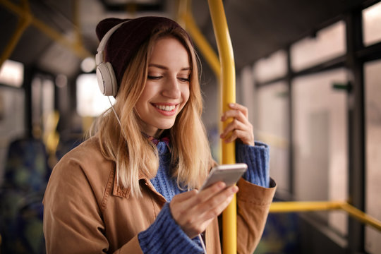 Young woman with headphones listening to music in public transport