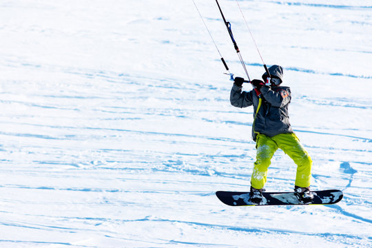 Snowboarder on a snowboard with snow kite is jimping above the fresh snow. Concept of outdoor extreme activities in winter snowkite