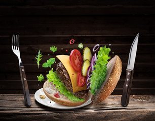 Hamburger ingredients falling down one by one to create a perfect meal. Colorful conceptual picture of burger cooking.