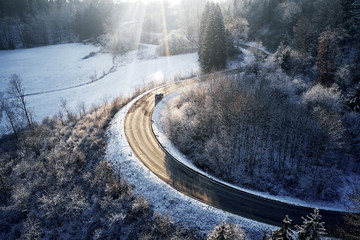 curved road in winter mountain landscape. Aerial view of forest and trees with a winding street surrounded by snow.