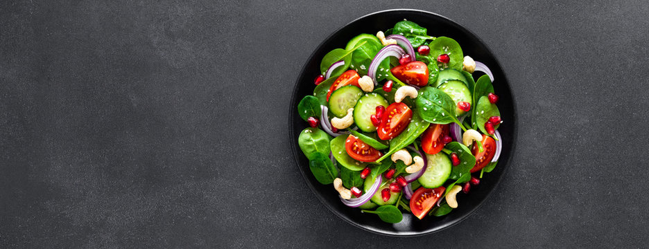 Spinach salad with fresh cucumbers, tomato, onion, pomegranate, sesame seeds and cashew nuts on black background. Healthy vegan food. Top view. Banner