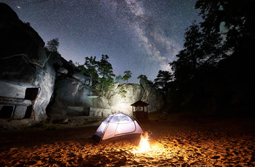 Camping at summer night near mountain rocks. White glowing tourist tent and bonfire under amazing night sky full of stars and Milky way. On the background beautiful starry sky, big boulders and trees